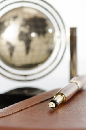 Pen, agenda and earth globe on office table against white background photo