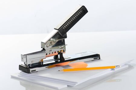 Large stapler, pencils, rubber and white papers against a  white background Stock Photo - 15139274