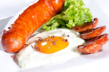Sausages, organic egg and lettuce on a white plate against a white background photo