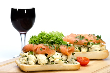 Sandwiches with salmon, organic egg omelette, lettuce and cherry and a glass of red wine  against a white backgroun photo
