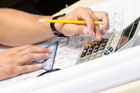 Man working with a calculator and square drawing on blueprints Stock Photo - 15934236