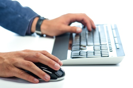 Mans hands working with computer mouse and  computer keyboard against white background