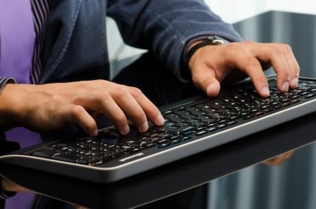 Mans hands working on computer keyboard