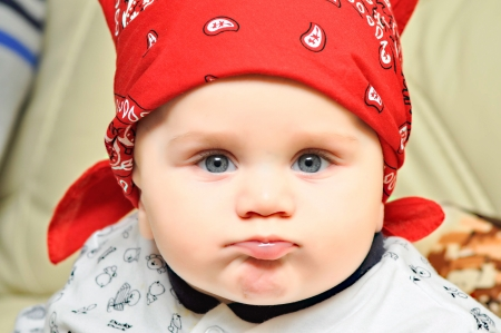 Baby boy with blue eyes and red scarf on the head grimacing photo