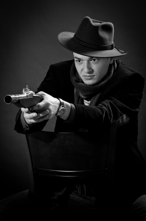 Young man with black hat aiming with a gun straight to the camera black and white Stock Photo - 16651096