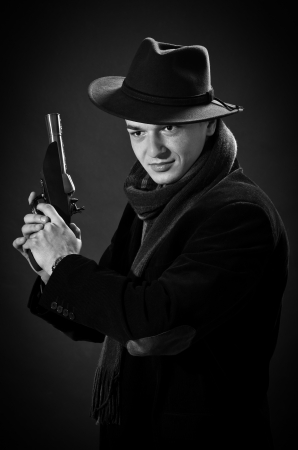 Young man with black hat aiming with a gun straight ti the camera  black and white Stock Photo - 16651100