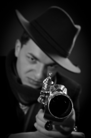 Young man with black hat aiming straight to the camera black and white photo