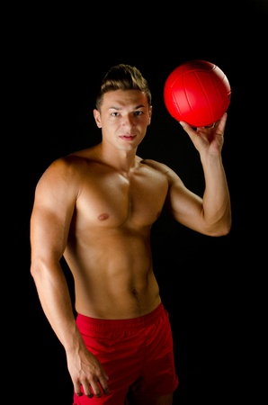 Man in a good shape holding a red volley ball Stock Photo - 16651300