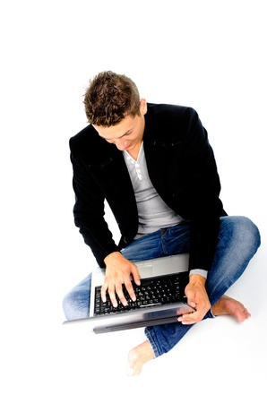 Young man working at laptop against white background