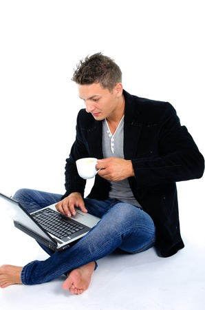 Young man working at laptop and drinking coffee against white background photo