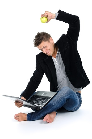 Angry young man working at laptop and eating apple agaisnt white background photo