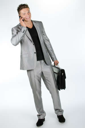Young man with briefcase and cell phone standing against white background Stock Photo - 16651139