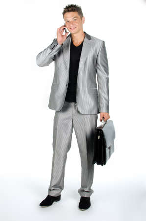 Young man with briefcase and cell phone standing against white background Stock Photo - 16651001