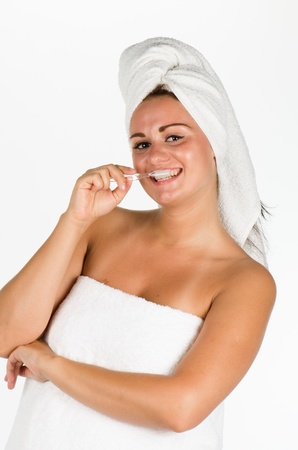 Portrait of young woman after bath brushing her teeth against white background photo