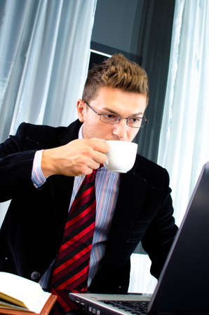 Young business man working in the office and drinking coffee Stock Photo - 16654723