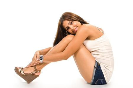 Side view of young woman sitting on floor against white background  photo