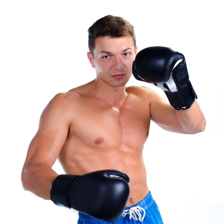 Muscular man boxing  against white background photo