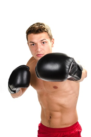Muscular man boxing  against white background