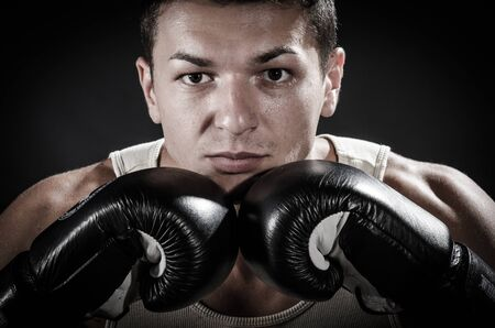 Muscular man showing his gloves against black background photo
