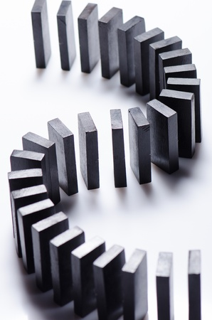 domino effect: Black dominoes in a row on white background  Stock Photo