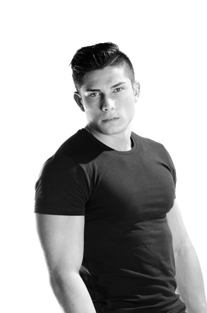 Image of muscular man posing in studio against white background black and white  photo