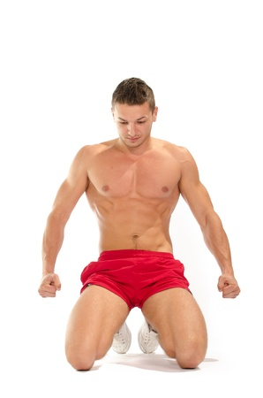 Portrait of young muscular man on his knees stretching against white background