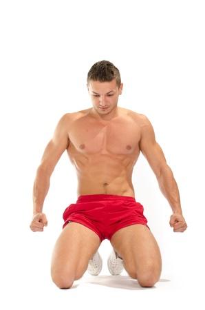 niño sin camisa: Retrato de hombre musculoso joven de rodillas extiende contra el fondo blanco