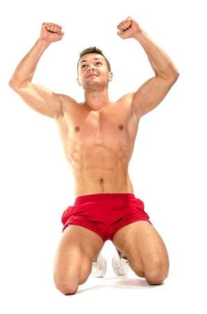 Portrait of young muscular man showing victory against white background  Stock Photo