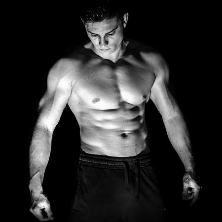 pantalones abajo: Retrato de hombre musculoso younng sin camisa sobre fondo negro