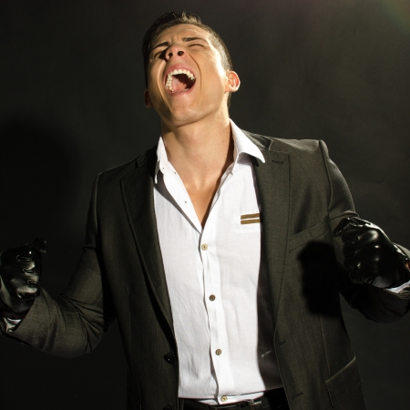 Angry young businness man screaming against black background  photo
