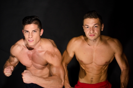 Two muscular men ready to fight against black background photo