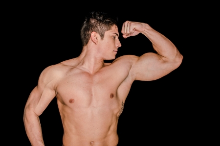 Muscular man showing his left arm against black background