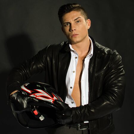 Passionate biker with his helmet against black background photo