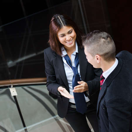 Business woman smiling and making gestures while talking to businessman Stock Photo - 16654405