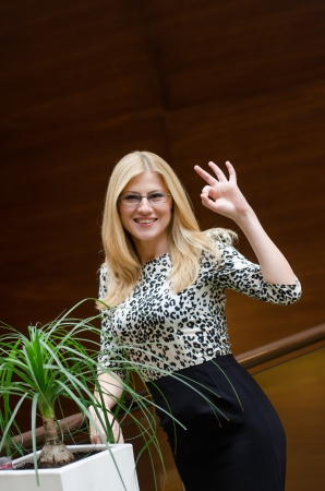 Business woman smiling and showing the ok sign in