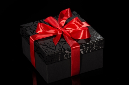 Black gift box with red ribbon against black background Stock Photo