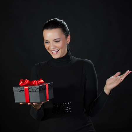 Happy beautiful woman with a black gift box against black background Stock Photo - 16681633