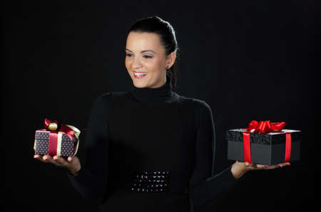 Happy beautiful woman holding gifts boxes in each hand against black background Stock Photo - 16681649