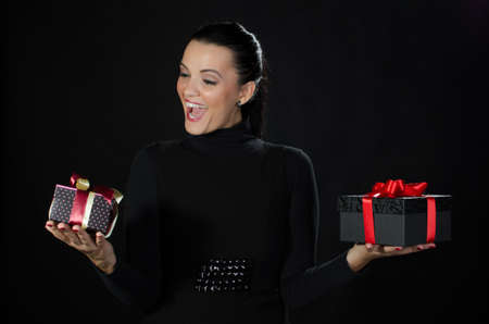 Happy beautiful woman holding gifts boxes in each hand against black background Stock Photo - 16681638