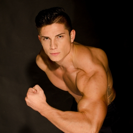 Muscular man showing his muscles against black background photo