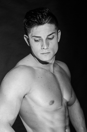 Muscular man  standing, looking down photo