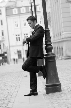 Groom watching his watch while waiting his bride black and white