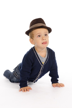 Portrait of child  with hat sitting on his knees and hands against white background  photo