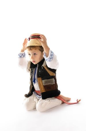 Portrait of beautiful child with traditional folk costume sitting on his knees  Stock Photo
