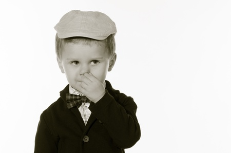 rubbing noses: Portrait of beautiful young child with hat and bow tie and rubbing his nose