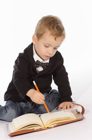 Portrait of young child with an notebook and pencil against white background