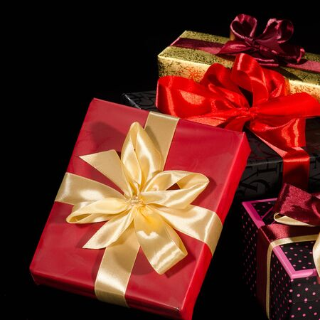 Colorful gift boxes isolated on black background closeup photo