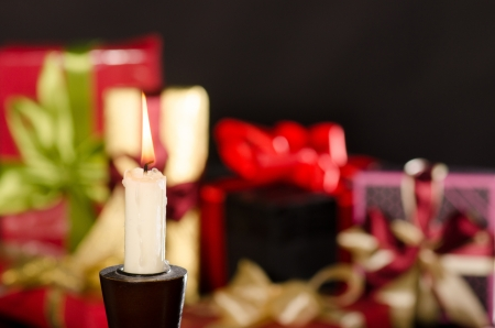 Candle and gifts boxes against black background photo
