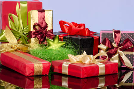 Colorful gift boxes and christmas arrangement against blue background photo
