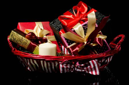 gift basket: Gifts basket and candle against black background